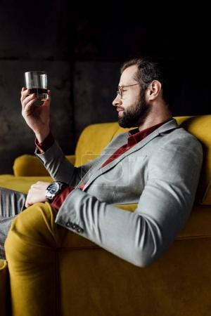 bearded handsome man looking at glass of whiskey
