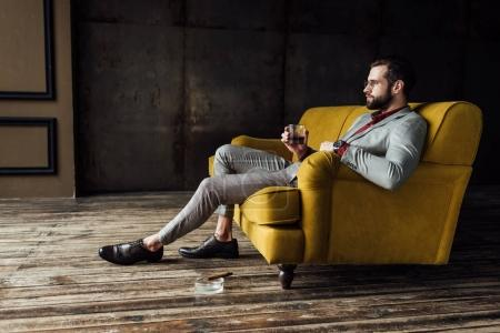 stylish man with glass of whiskey sitting on couch with cigar in ashtray on floor