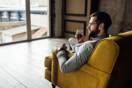 fashionable man holding glass of whiskey and sitting on sofa