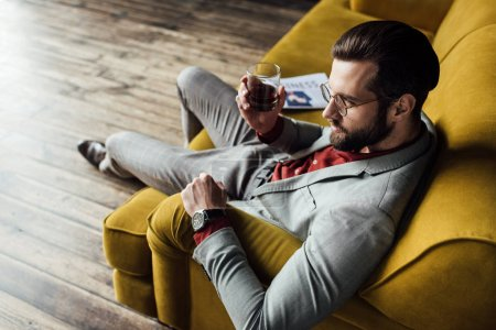 stylish man with whiskey sitting on sofa with newspaper