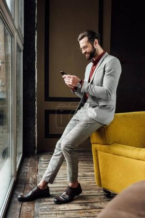 Photo for Stylish handsome man using smartphone and sitting at window - Royalty Free Image