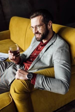 handsome smiling man in eyeglasses holding glass of whiskey
