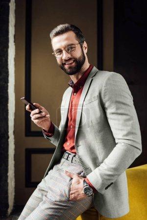 cheerful fashionable handsome man using smartphone
