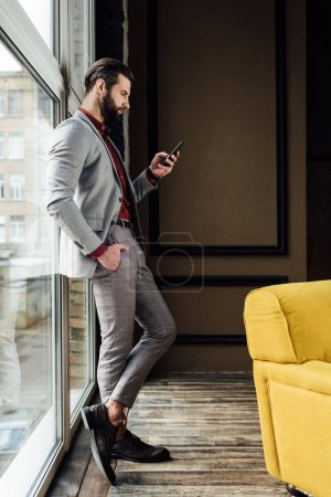 fashionable man in suit using smartphone at window