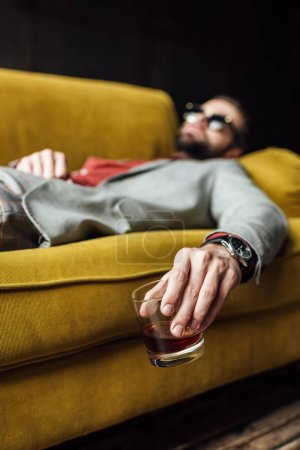 selective focus of drunk man with glass of whiskey sleeping on yellow sofa