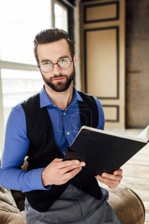 fashionable elegant businessman in eyeglasses holding notebook in loft interior