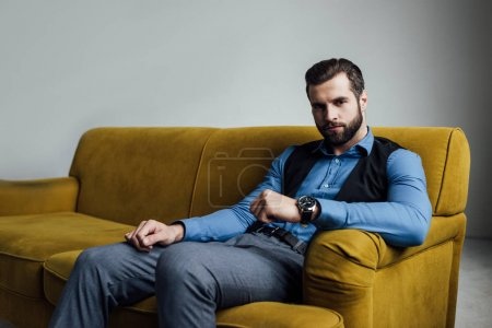 stylish elegant man sitting on yellow sofa
