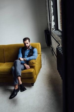 Photo pour À la mode homme élégant assis sur un canapé jaune dans loft - image libre de droit