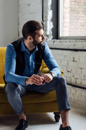 Photo pour Homme à la mode caucasien tenant du whisky et assis sur un canapé jaune - image libre de droit
