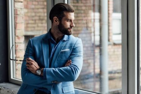Photo pour Cher homme en costume bleu tendance tenant des lunettes et regardant la fenêtre - image libre de droit