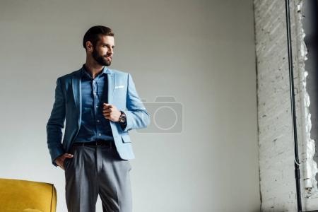 elegant handsome man in blue trendy suit looking at window