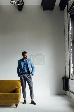 Photo pour Gentil homme élégant posant en costume tendance bleu et regardant la fenêtre - image libre de droit