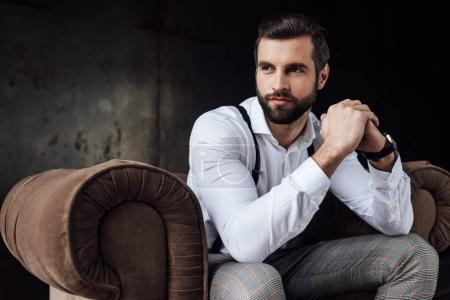 Photo for Handsome bearded man thinking and sitting in armchair - Royalty Free Image