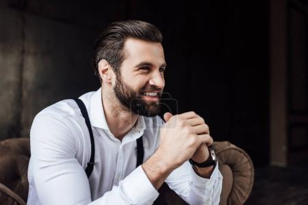 handsome stylish smiling man sitting in armchair