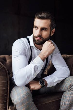 stylish man in suspenders thinking and sitting in armchair