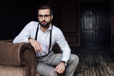 Photo pour Barbu à la mode dans les verres et les bretelles assis dans le fauteuil - image libre de droit