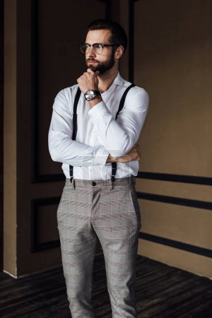 Photo for Pensive fashionable man in trendy suspenders - Royalty Free Image