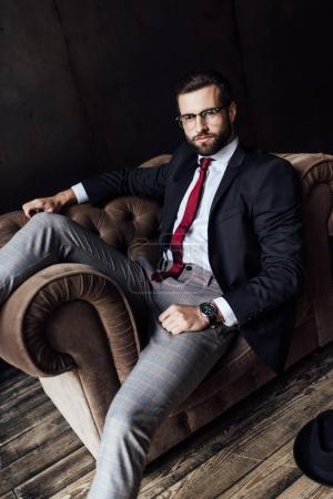handsome businessman in stylish suit posing on armchair