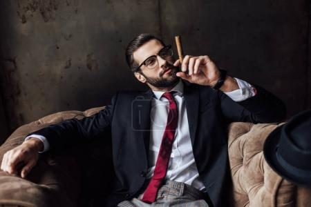 fashionable man sitting in armchair and holding cigar