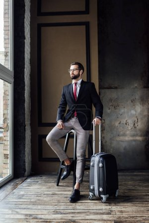 elegant businessman in suit posing on stool with luggage