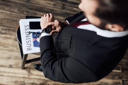 selective focus of businessman looking at watch while standing at stool with business newspaper and smartphone