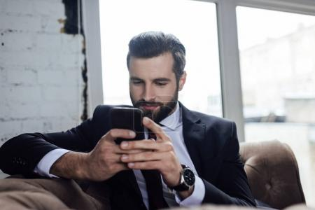 handsome bearded businessman using smartphone