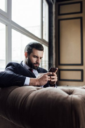 fashionable bearded businessman messaging on smartphone while sitting in armchair