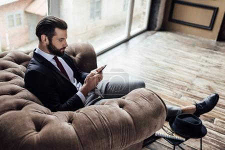 confident elegant businessman using smartphone and sitting in armchair