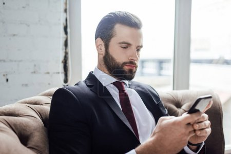 bearded businessman messaging on smartphone and sitting in armchair