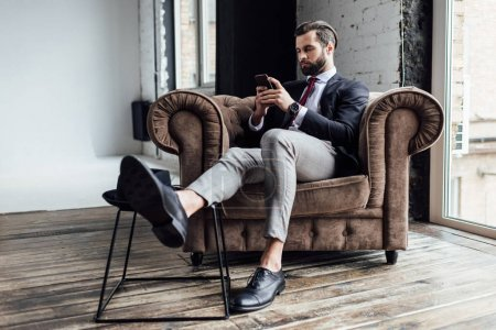 stylish businessman using smartphone and sitting in armchair in loft