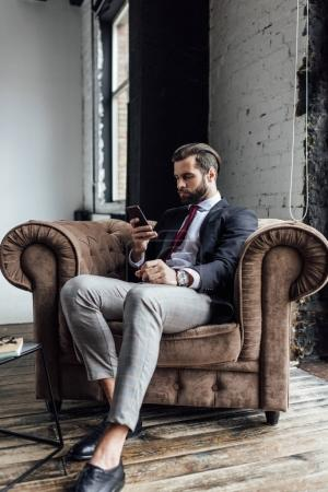 confident businessman texting sms on smartphone while sitting in armchair in loft