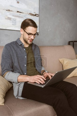 happy stylish man working with laptop on couch