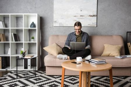 Photo for Young happy freelancer working with laptop while sitting on couch - Royalty Free Image