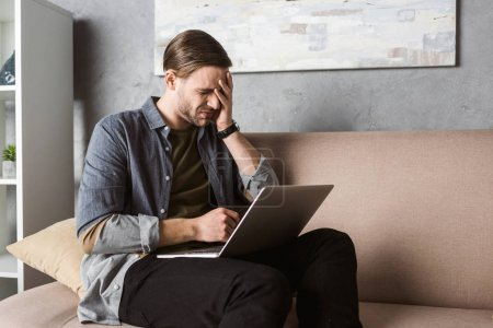 young overworked man with laptop having headache while sitting on couch