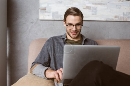 happy young businessman working with laptop on couch
