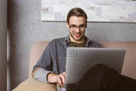 Photo for Happy young businessman working with laptop on couch - Royalty Free Image
