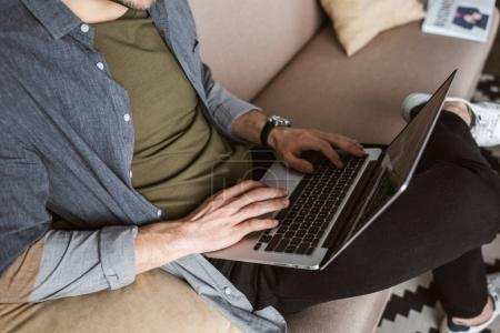 cropped shot of man working with laptop on couch