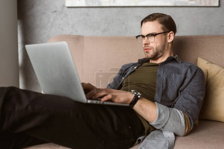 serious young man working with laptop on couch