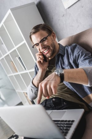 angry young man talking by phone and pointing at laptop