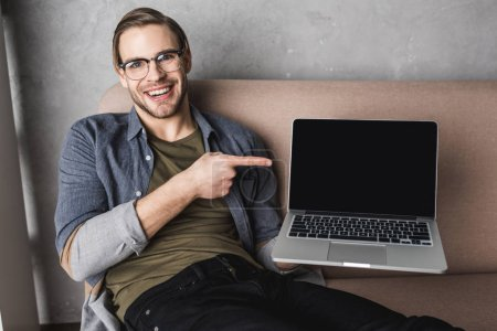 young smiling man sitting on couch and pointing at laptop screen