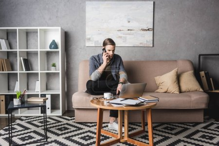 young handsome man working with laptop on couch and talking by phone