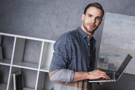 Photo pour Jeune homme d'affaires beau avec ordinateur portable au bureau moderne - image libre de droit
