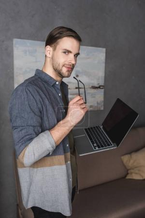 Photo pour Jeune homme d'affaires élégant avec ordinateur portable au bureau moderne - image libre de droit
