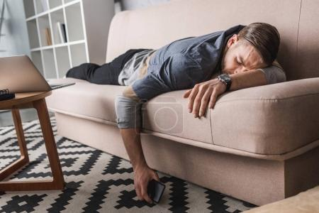 exhausted young man sleeping on couch with smartphone in hand