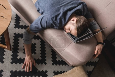high angle view of overworked businessman sleeping on couch with head lying on laptop