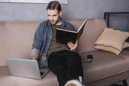 young serious businessman reading notes on couch and using laptop