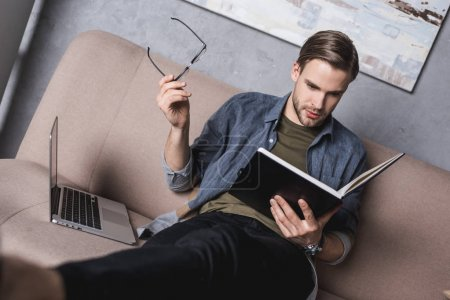 young serious businessman reading notes on couch