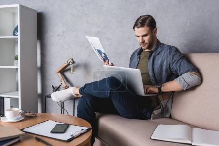 Photo pour Jeune homme d'affaires travaillant avec portable sur canapé - image libre de droit