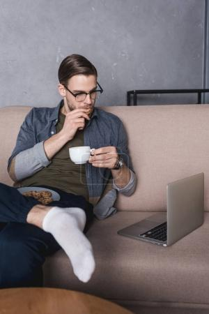 young handsome man working with laptop on couch while eating cookies with coffee