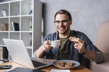 young handsome man working with laptop and eating cookies and coffee